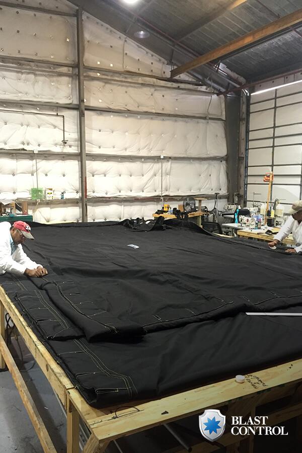 Two Men Working on Blast Curtain